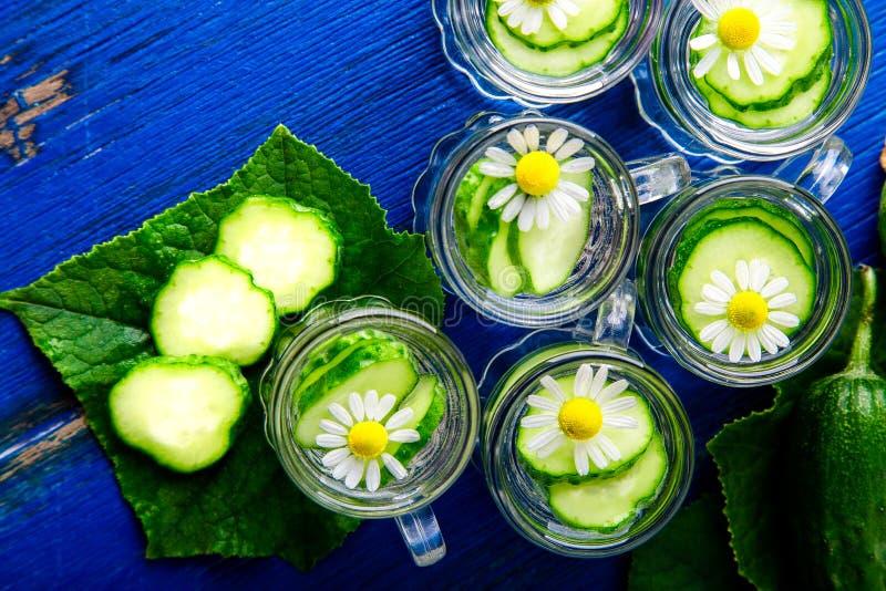 Acqua del cetriolo in sei barattoli di vetro del piccolo muratore su fondo blu rustic Vista superiore detox fotografia stock
