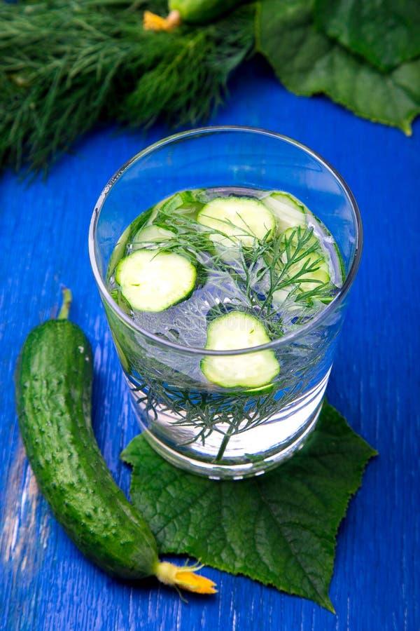 Acqua del cetriolo in vetro con aneto su fondo di legno blu Disintossicazione, dieta fotografia stock