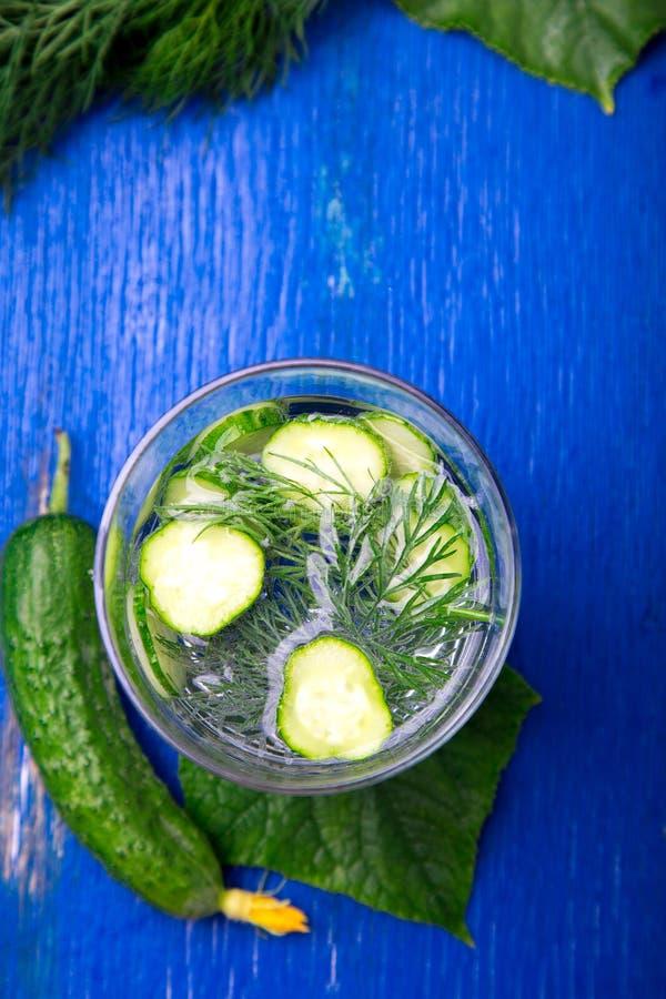 Acqua del cetriolo in vetro con aneto su fondo di legno blu Disintossicazione, dieta Vista superiore Copi lo spazio immagini stock