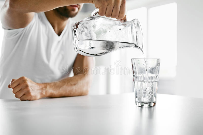 Acqua della bevanda Chiuda sull'acqua di versamento dell'uomo in vetro idratazione fotografie stock