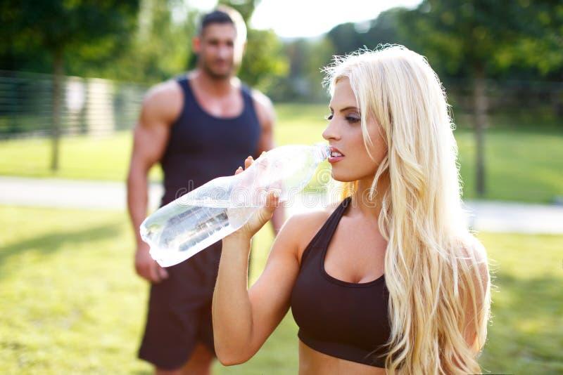 Acqua della bevanda della donna dopo l'allenamento dalla bottiglia immagine stock