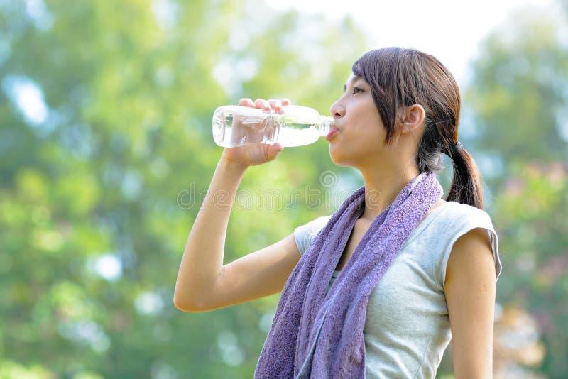 Acqua della bevanda della donna dopo lo sport immagine stock libera da diritti
