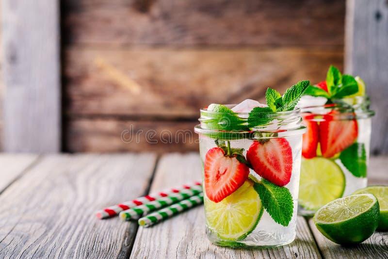 Acqua della disintossicazione con la fragola, la calce e la menta Cocktail o limonata ghiacciato di estate in barattolo di murato immagine stock
