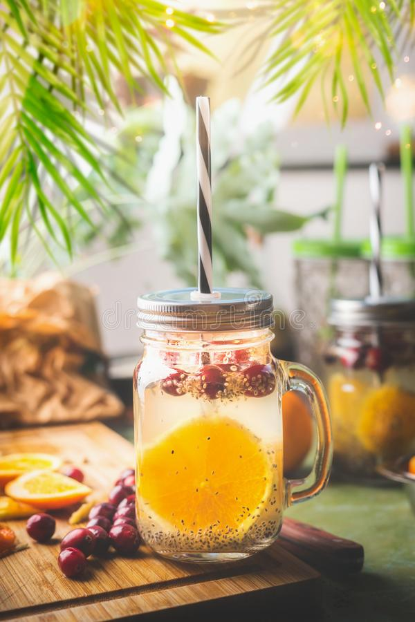 Acqua della disintossicazione dei semi di Chia con la fetta della frutta, il succo di limone ed i mirtilli rossi arancio in barat immagini stock