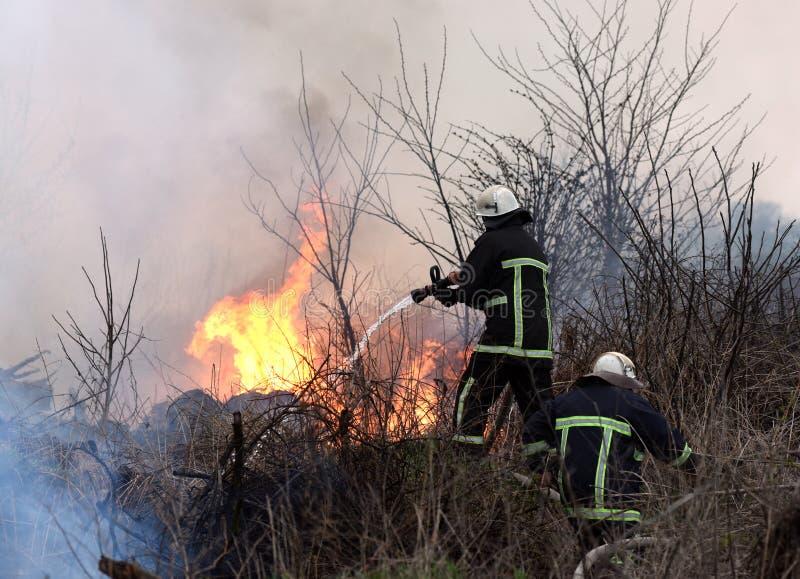 Acqua dello spruzzo dei pompieri all'incendio violento il pompiere estingue la a fotografia stock libera da diritti