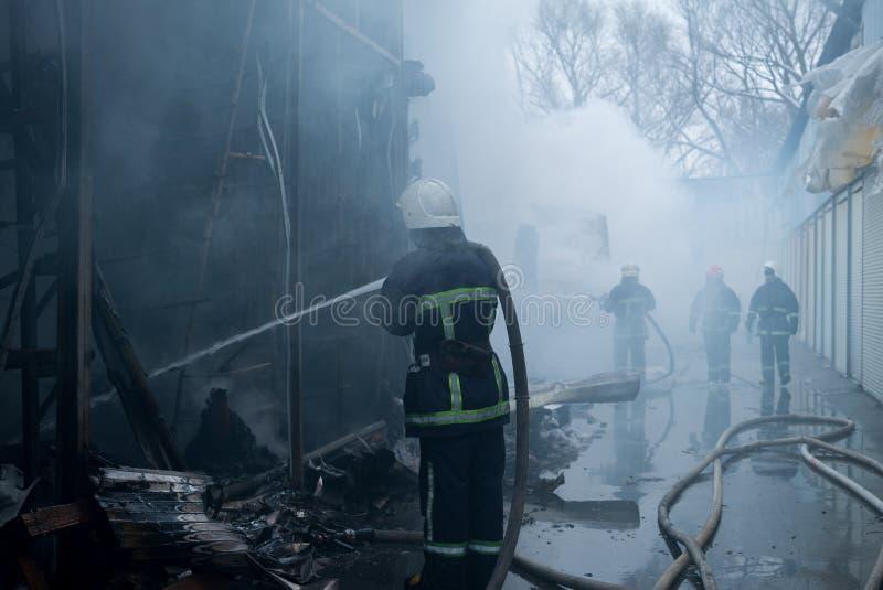 Acqua dello spruzzo dei pompieri Fumo e buiding dopo il fuoco immagini stock