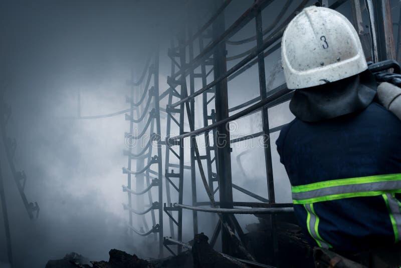 Acqua dello spruzzo dei pompieri Fumo e buiding dopo il fuoco immagine stock libera da diritti
