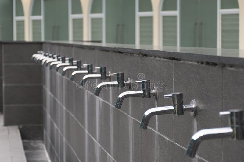 Acqua di molti rubinetti senza acqua nel Masjid per il gioco musulmano fotografia stock libera da diritti