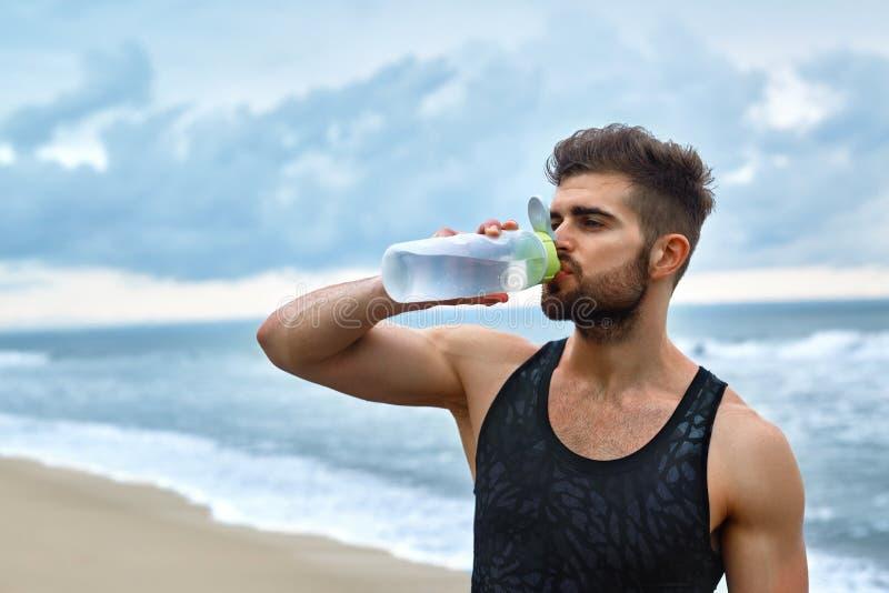 Acqua di rinfresco bevente dell'uomo dopo l'allenamento alla spiaggia bevanda immagini stock