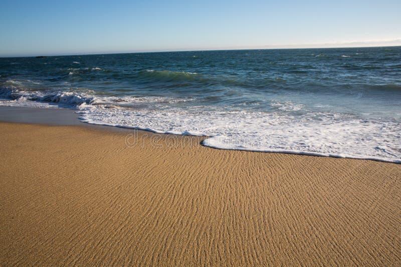 Acqua di ritirata su una spiaggia fotografia stock