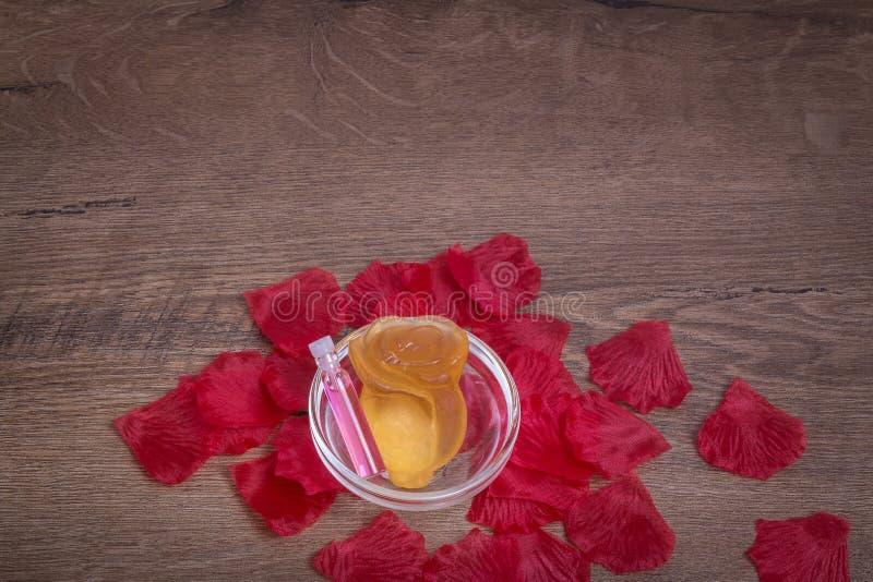Acqua di rose profumata e fiore rosa fatti di sapone in cristalleria sulla tavola di legno immagini stock