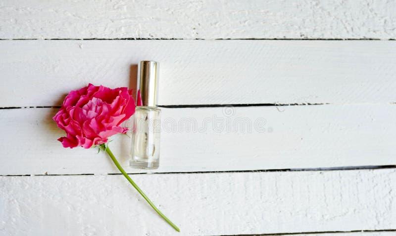Acqua di rose profumata in una bottiglia su una tavola di legno Copi lo spazio immagine stock