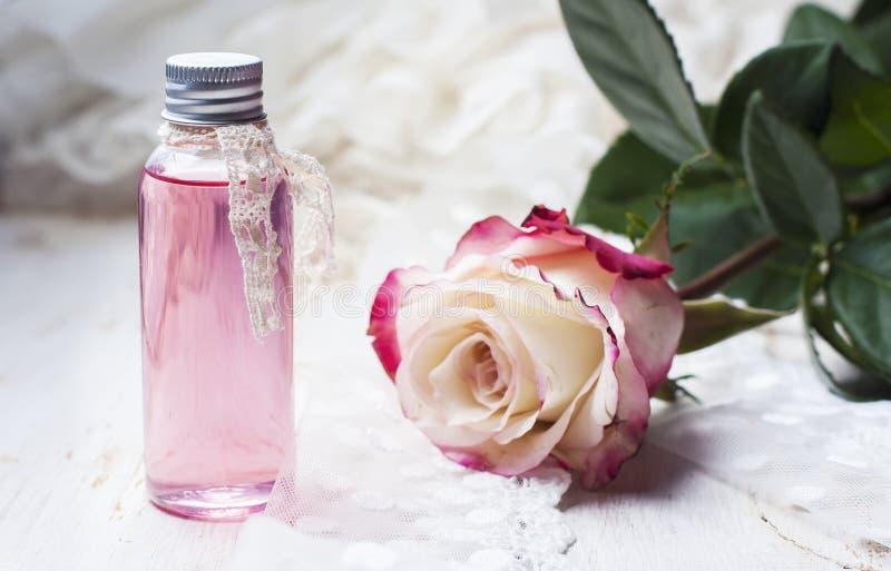 Acqua di rose profumata in una bottiglia su una tavola di legno fotografia stock libera da diritti