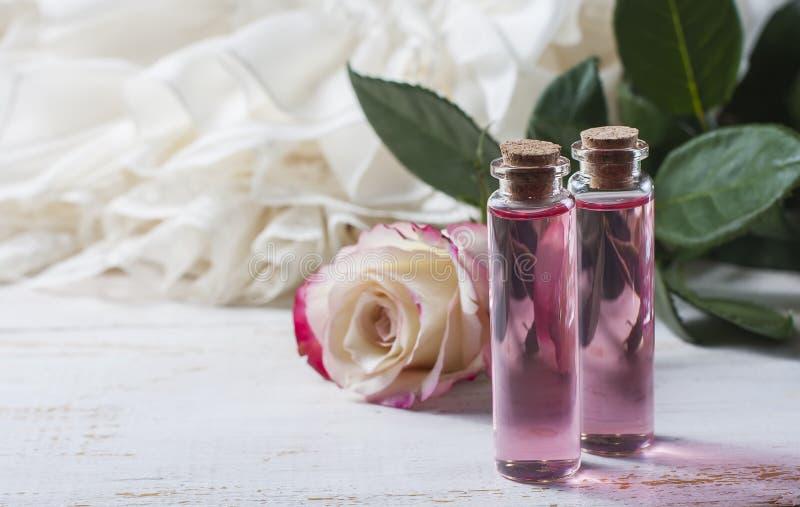 Acqua di rose profumata in una bottiglia su una tavola di legno fotografie stock