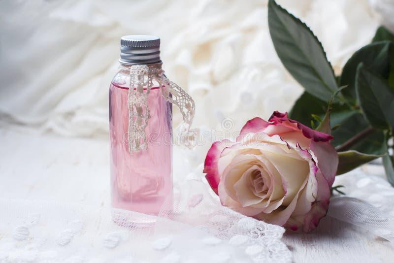 Acqua di rose profumata in una bottiglia su una tavola di legno fotografia stock
