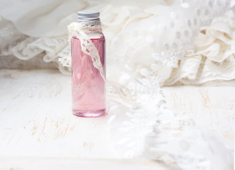Acqua di rose profumata in una bottiglia su una tavola di legno fotografie stock libere da diritti