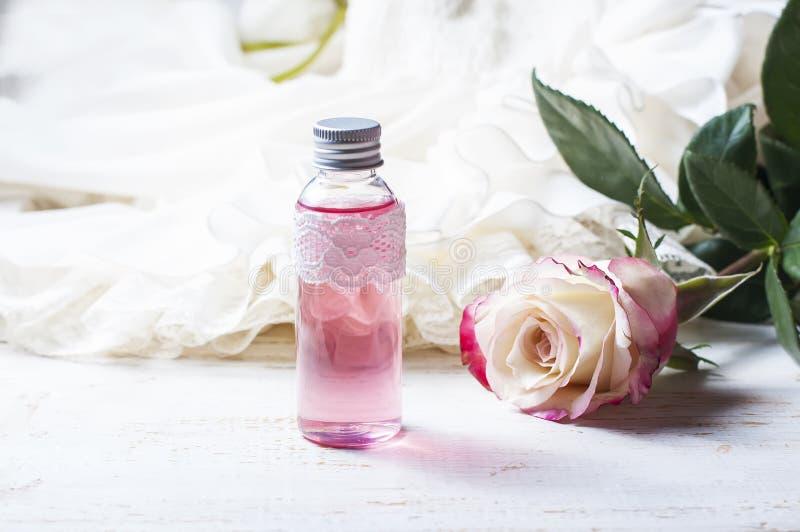 Acqua di rose profumata in una bottiglia su una tavola di legno immagini stock libere da diritti