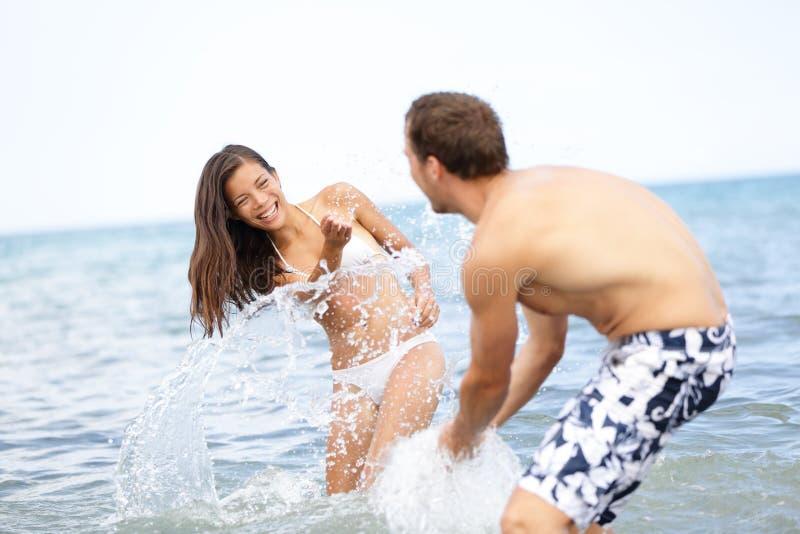 Acqua di spruzzatura allegra delle coppie di divertimento di estate della spiaggia fotografia stock