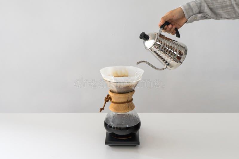 Acqua di versamento alla caffettiera sulla parete bianca fotografia stock