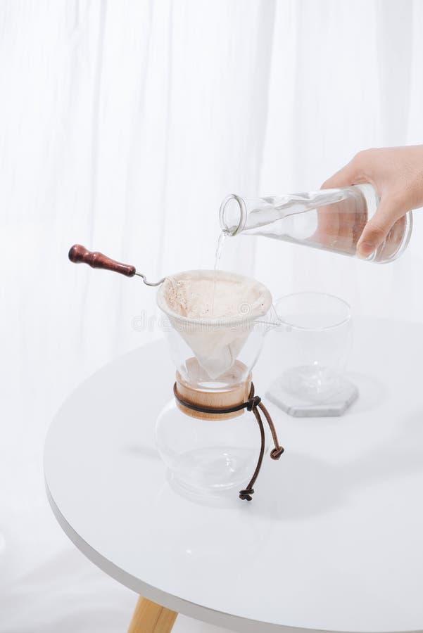 Acqua di versamento alla caffettiera sulla parete bianca e sulla Tabella bianca, miscela manuale, caffè americano della mano fotografie stock