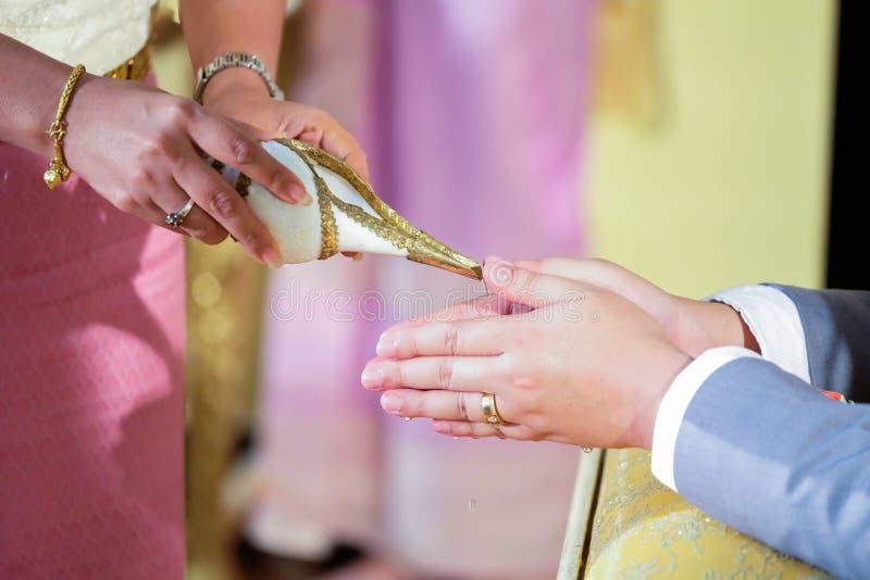 Acqua di versamento dalla conchiglia di strombo nelle mani della sposa a T fotografia stock