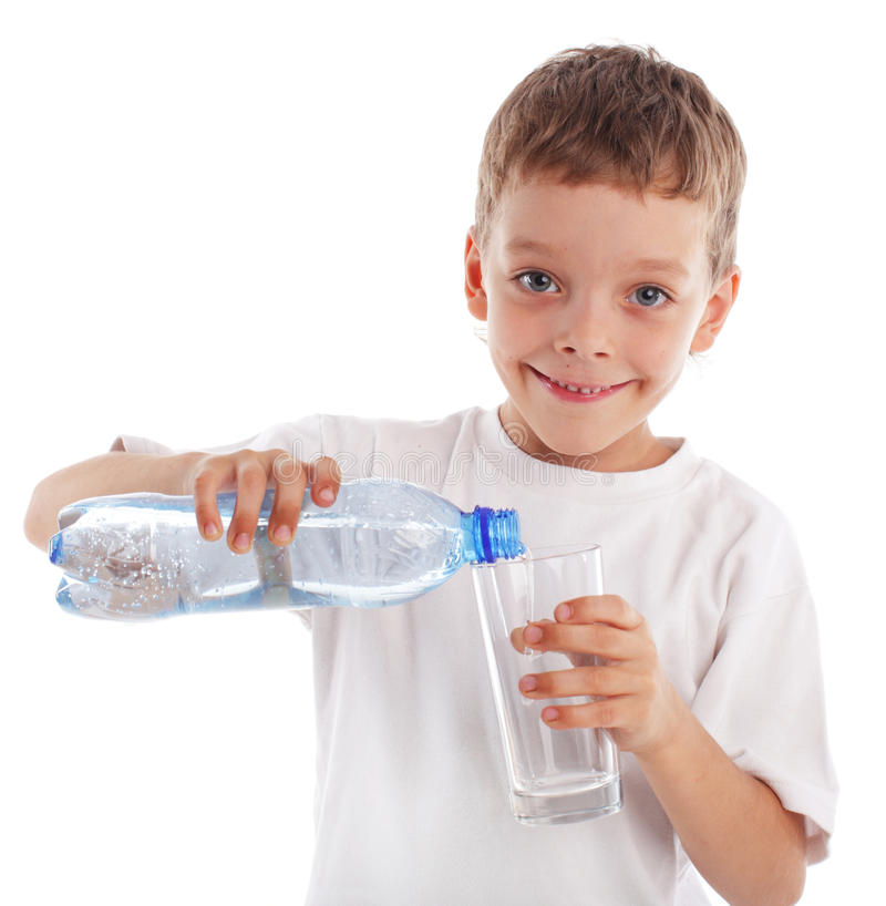 Acqua di versamento del ragazzo in un vetro fotografia stock