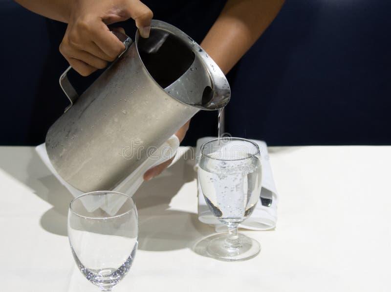 Acqua di versamento nei vetri, servizio del cameriere dei ristoranti fotografia stock