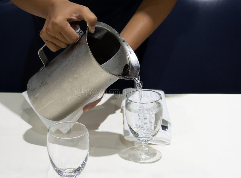 Acqua di versamento nei vetri, servizio del cameriere dei ristoranti immagine stock libera da diritti