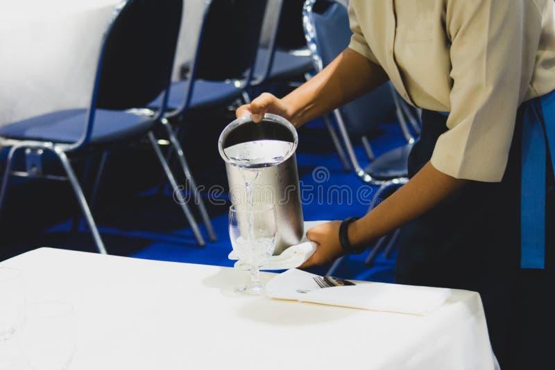 Acqua di versamento nei vetri, servizio del cameriere dei ristoranti fotografia stock libera da diritti