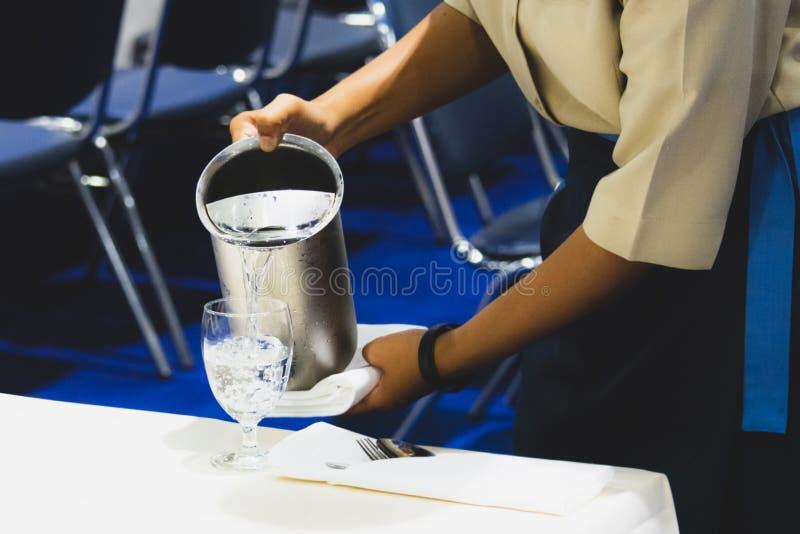 Acqua di versamento nei vetri, servizio del cameriere dei ristoranti fotografie stock libere da diritti