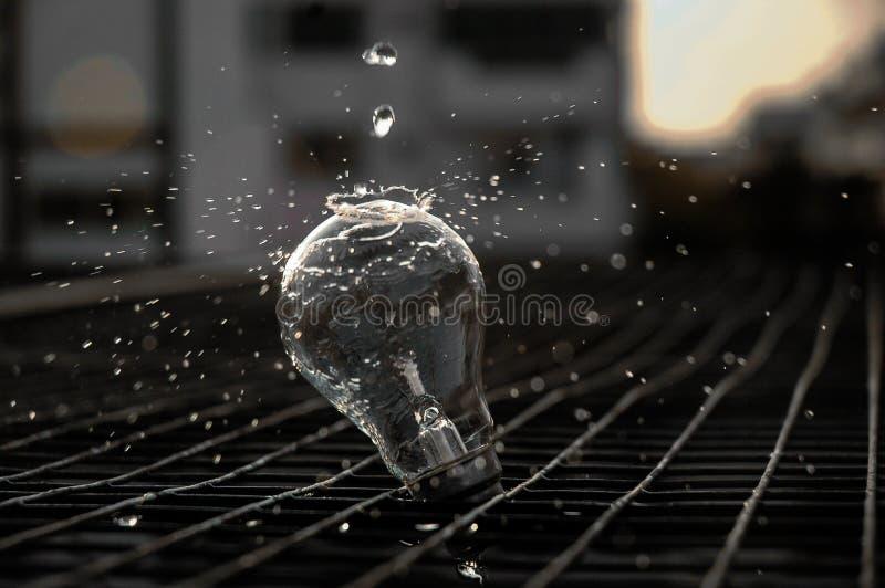 Acqua di versamento su una lampadina fotografia stock libera da diritti