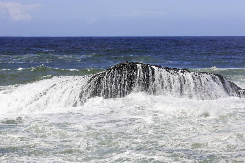 Acqua ed onde spumose sopra una roccia nel mare fotografia stock libera da diritti