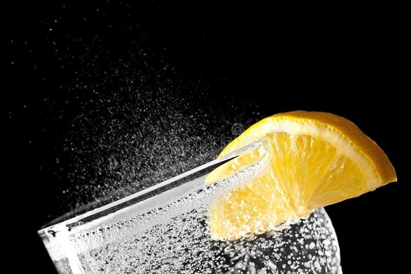 Acqua frizzante con una fetta arancio isolata su backgroun nero immagini stock libere da diritti