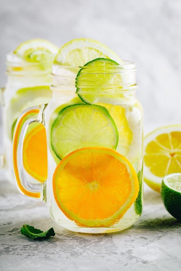 Acqua infusa della disintossicazione con le fette della limetta, del limone e delle arance con la menta Cocktail freddo ghiacciat fotografia stock libera da diritti