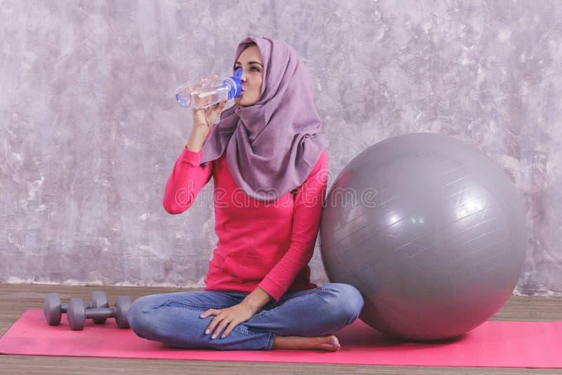 Acqua minerale bevente della bella donna in buona salute dopo avere fatto yoga fotografia stock libera da diritti