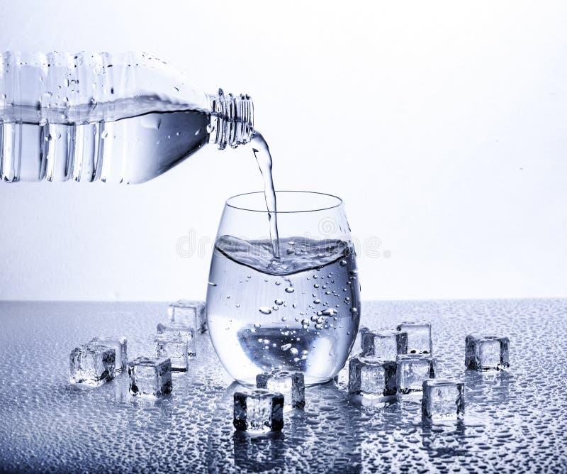 Acqua minerale bevente fresca di versamento dalla bottiglia di plastica fotografie stock libere da diritti