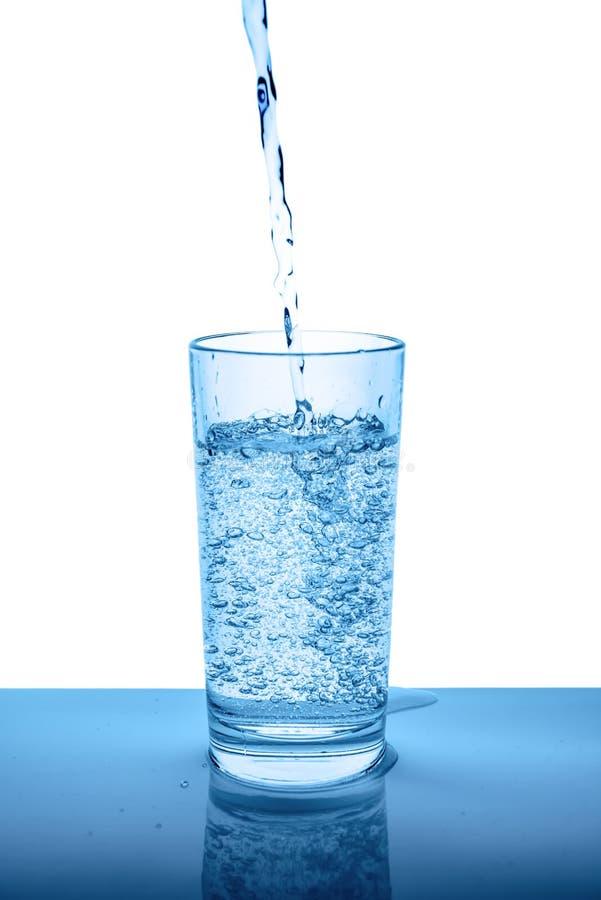 Acqua minerale di versamento in vetro trasparente con le gocce e la bolla fotografie stock libere da diritti