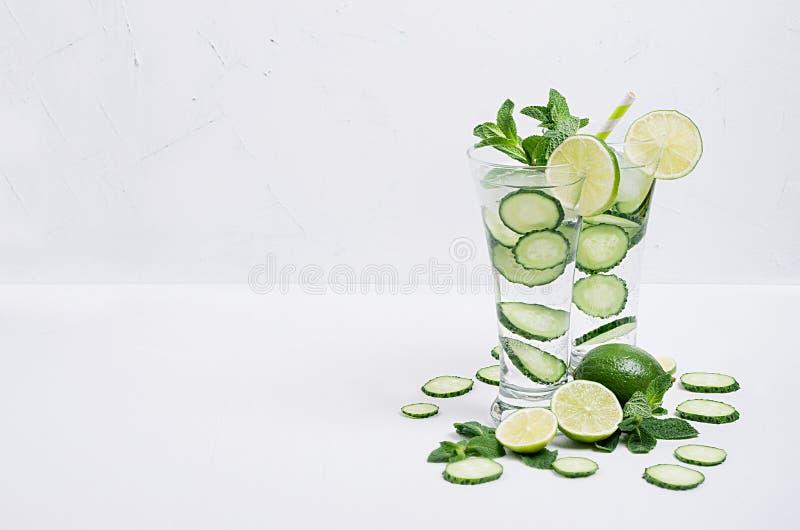 Acqua minerale fredda con le fette cetriolo, calce, menta e ghiaccio su fondo bianco molle, spazio della copia Bevande di rinfres fotografia stock