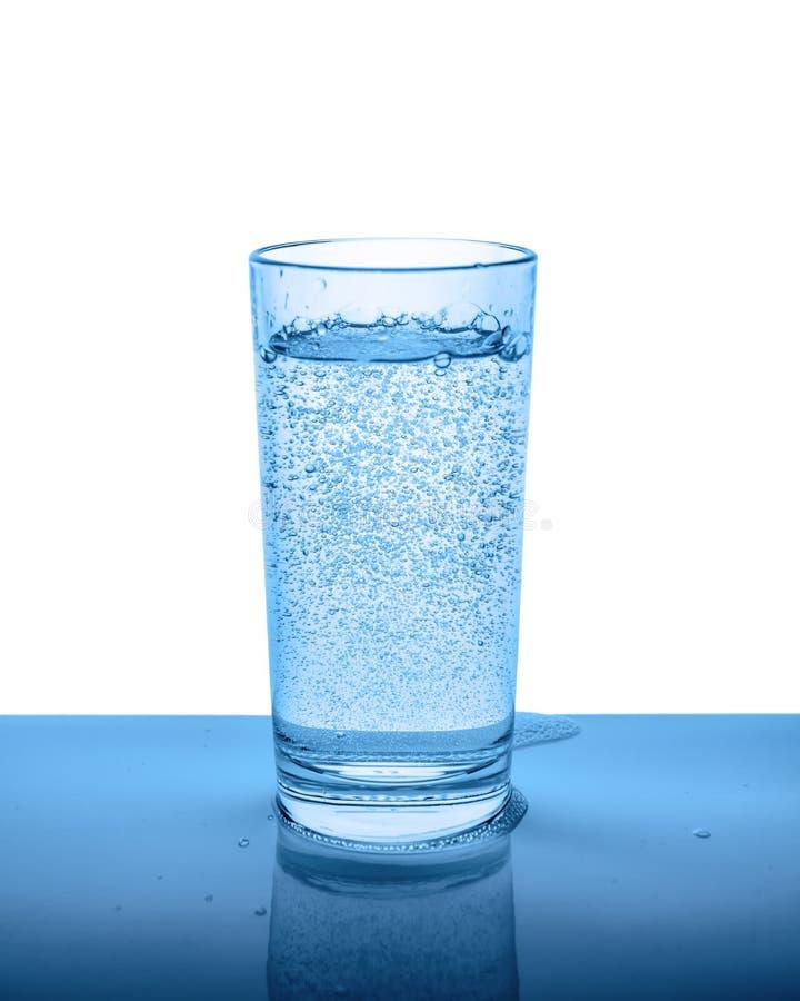 Acqua minerale in vetro trasparente con le gocce e il isolat delle bolle immagini stock libere da diritti