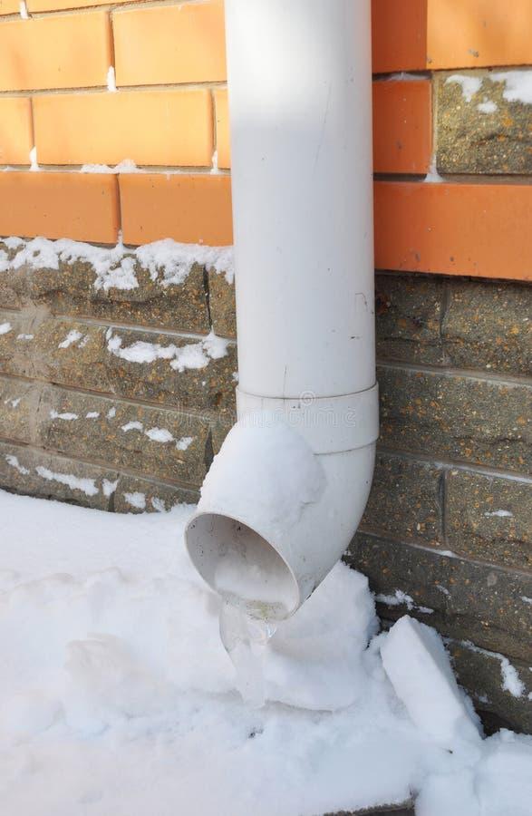Acqua piovana congelata che vuota la discesa di colata della grondaia Becco della grondaia in Wint fotografie stock
