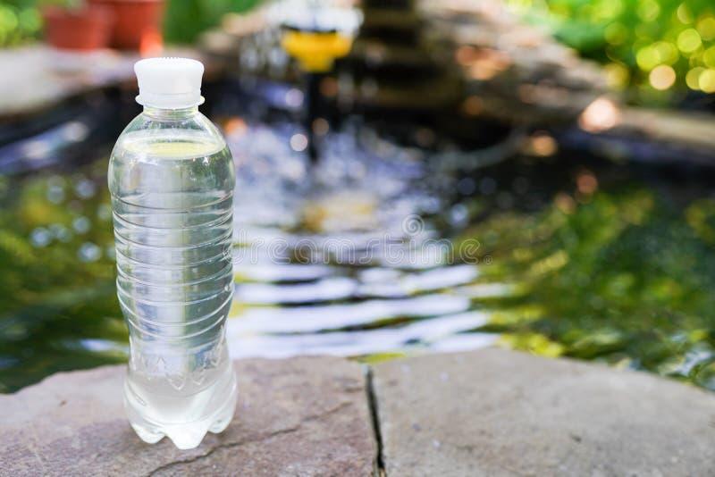 Acqua potabile che versa dalla bottiglia sul fondo verde vago della natura fotografia stock libera da diritti