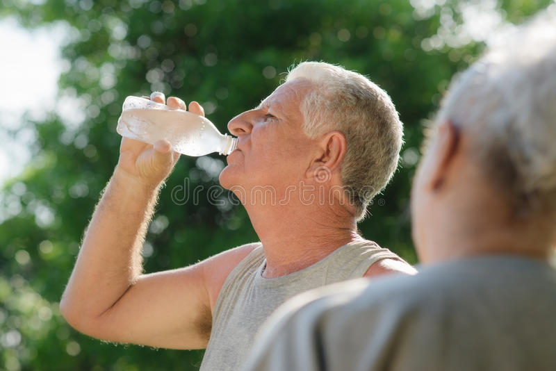 Acqua potabile degli anziani dopo forma fisica in sosta fotografia stock