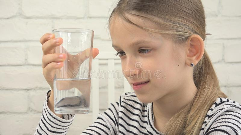 Acqua potabile del bambino, bambino assetato che studia vetro di acqua dolce, ragazza in cucina immagine stock