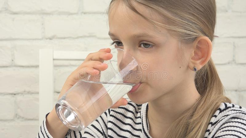 Acqua potabile del bambino, bambino assetato che studia vetro di acqua dolce, ragazza in cucina immagini stock libere da diritti