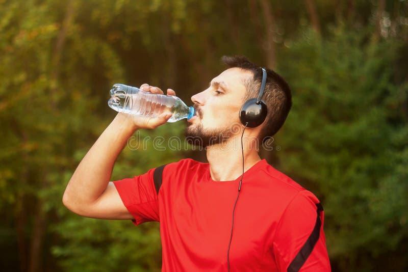 Acqua potabile del giovane uomo atletico all'aperto nel parco fotografie stock libere da diritti