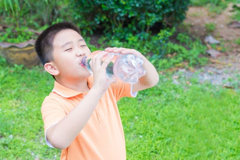 Acqua potabile del ragazzo asiatico dalla bottiglia immagine stock libera da diritti
