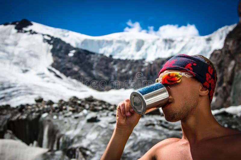 Acqua potabile dell'alpinista maschio da una tazza su un ghiacciaio nel extre di vacanze dell'attivo di avventura di concetto di  immagine stock libera da diritti