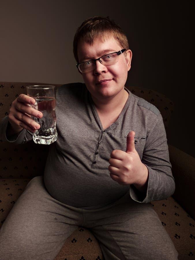 Acqua potabile dell'uomo di peso eccessivo fotografia stock libera da diritti