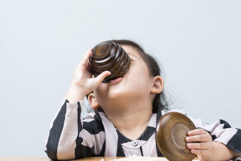 Acqua potabile della bambina tailandese asiatica sveglia dalla tazza di tè immagini stock