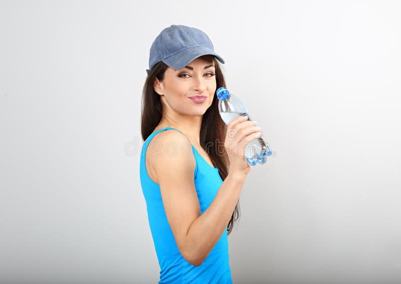 Acqua potabile della bella donna esile sportiva felice dalla bottiglia dopo la formazione sul fondo blu dello studio fotografie stock